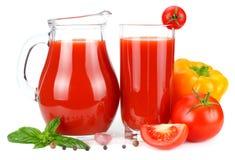 Jus de tomates dans la cruche en verre avec la tomate, l'ail, les épices, et le basilic d'isolement sur le fond blanc Images stock