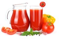 Jus de tomates dans la cruche en verre avec la tomate, l'ail, les épices, et le basilic d'isolement sur le fond blanc Photographie stock libre de droits
