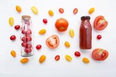 Jus de tomates en bouteille et tomates fraîches sur le dos en bois blanc Images stock