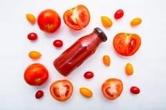 Jus de tomates frais dans la bouteille et tranches fraîches de tomates sur le petit morceau Photographie stock