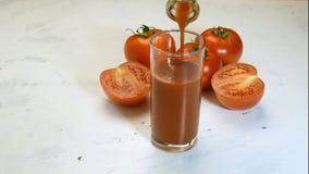 Jus de tomates frais versant d'une cruche dans un verre à boire clips vidéos