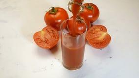Jus de tomates frais versant d'une cruche dans un verre à boire banque de vidéos