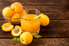 Jus et abricots frais d'abricot sur la table en bois Photographie stock