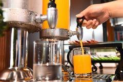 Jus et eau d'orange dans le refroidisseur d'eau Photo stock