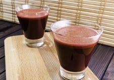 Jus frais de carotte et de betteraves en verre sur le foyer sélectif en bois de fond de plateau et de bambou modifié la tonalité Images stock