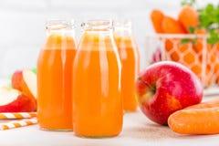 Jus frais de carotte et de pomme sur le fond blanc Jus de carotte et de pomme dans des bouteilles en verre sur la table blanche,  Photo libre de droits