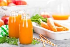 Jus frais de carotte et de pomme sur le fond blanc Jus de carotte et de pomme dans des bouteilles en verre sur la table blanche J Images libres de droits