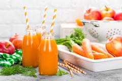 Jus frais de carotte et de pomme sur le fond blanc Jus de carotte et de pomme dans des bouteilles en verre sur la table blanche J Image libre de droits