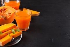 Jus frais de potiron dans de beaux verres et cruche avec des morceaux de légume mûr sur le fond en bois brun Jus d'orange douce H Photographie stock