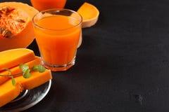 Jus frais de potiron dans de beaux verres et cruche avec des morceaux de légume mûr sur le fond en bois brun Jus d'orange douce H Images stock