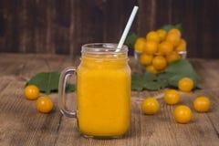 Jus jaune de prune dans un verre et une prune jaune mûre sur une table en bois de vintage Bio nourriture et boisson saines Régime Images libres de droits