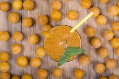 Jus jaune de prune dans un verre et une prune jaune mûre sur une table en bois de vintage Bio nourriture et boisson saines Régime Photo libre de droits