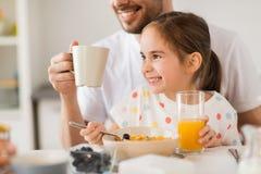 Jus potable de famille heureuse pour le petit déjeuner à la maison Images libres de droits