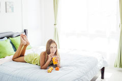Jus potable de fille et détente dans la chambre à coucher Image libre de droits