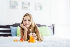 Jus potable de fille et détente dans la chambre à coucher Photographie stock libre de droits