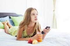 Jus potable de fille et TV de observation dans la chambre à coucher Image libre de droits