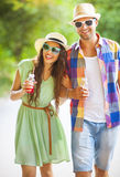 Jus potable et marche de jeunes couples heureux Images libres de droits