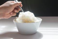 Jusmine coció el arroz al vapor, en el cuenco blanco que tomaba con la cuchara imagen de archivo
