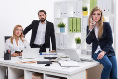 Just another day in office. Man standing near boss's armchair, women talking on phone sitting on desk. Office employees' portrait. Concept of collaboration Stock Photo