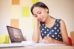 Just another day at the office. A young woman writing while sitting in her office Stock Image