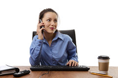 Just another day at work. Woman working at her desk on a mobile phone royalty free stock images