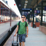 Just arrived: handsome young man walking along a platform Royalty Free Stock Photos