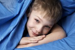 Just awakened. Boy in blue bedclothes royalty free stock image