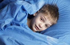 Just awakened. Boy in blue bedclothes stock photo
