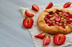 Just baked strawberry tart on the gray concrete background with copy space. Vegetarian healthy rhubarb galette. Decorated with fresh sliced strawberries Royalty Free Stock Image