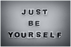 Just Be Yourself. Paper letters. Black and white image with vignette and white frame stock photo