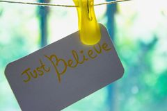 `Just believe` card hanging on the wire,  background - light behind the bars. Concept - always believe. Even when the way is with obstacles, there is always Stock Images