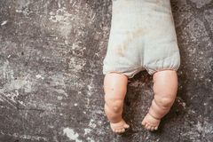 Just the bottom half of an old doll abandoned on a concrete floo Stock Image