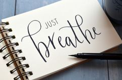 JUST BREATHE hand-lettered in notepad. JUST BREATHE hand-lettered in notebook on blue wooden desk with pen and cup of coffee royalty free stock photos