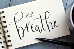 JUST BREATHE hand-lettered in notepad with brush pen. And cup of coffee on retro blue wooden background royalty free stock image