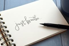 JUST BREATHE hand-lettered in notepad with brush pen. On retro blue wooden background royalty free stock photography