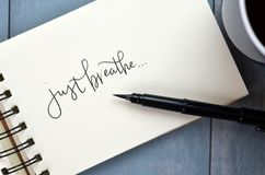 JUST BREATHE hand-lettered in notepad. JUST BREATHE hand-lettered in notebook on blue wooden desk with pen royalty free stock photos