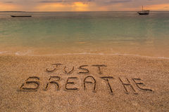 Just breathe. In the picture a beach at sunset with the words on the sand Just breathe Royalty Free Stock Photography
