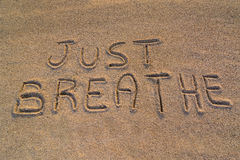 Just breathe symbol. In the picture the words on the sand Just breathe Stock Images
