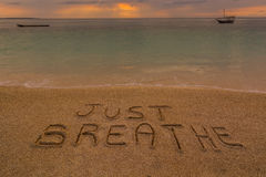 Just breathe words. In the picture a beach at sunset with the words on the sand Just breathe Royalty Free Stock Image