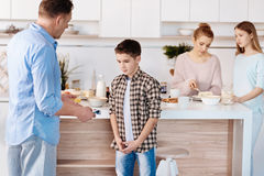 Just caring father punishing his son in the kitchen Royalty Free Stock Photos