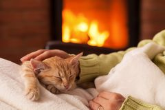 Free Just Chilling By The Fireplace - Woman Hands Petting A Small Tabby Cat Royalty Free Stock Photos - 165232948