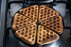 Just cooked, delicious, tasty, hot yogurt pancakes on waffle iron on fire stove in kitchen. royalty free stock photography