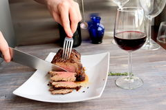 Just cooked roast beef is sliced by young chef on the white plate. Stock Image