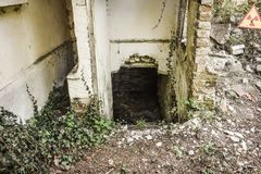 Just discover hidden underground rooms behind the broken wall of the abandoned old building with radioaactive sign in the area. royalty free stock images