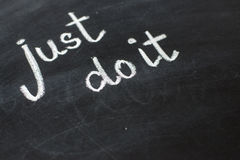 Just do it, handwritten with white chalk on a blackboard. Royalty Free Stock Image
