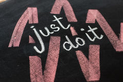 Just do it, handwritten with white chalk on a blackboard. Royalty Free Stock Photos