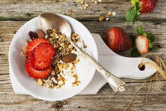 Just an early breakfast at home with oatmeal, milk, strawberries and almonds on a simple wooden background Royalty Free Stock Photography