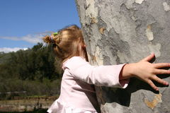 Just feels good!. Young girl with her arms around a sycamore tree stock photo