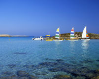 Just fun. Bright pleasure sailboats by rocks in the shallow water of Nissi Beach, Cyprus royalty free stock image