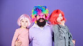 Just for fun. Party time. How crazy is your father. Man bearded father and kids girls wear colorful wig violet stock images